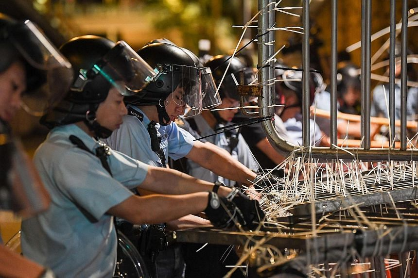 Officers clearing the barricades outside the police headquarters early yesterday morning. The protesters had set up the barricades secured with cable ties to cut off access to the complex. Some security and police personnel cleaning and covering up t