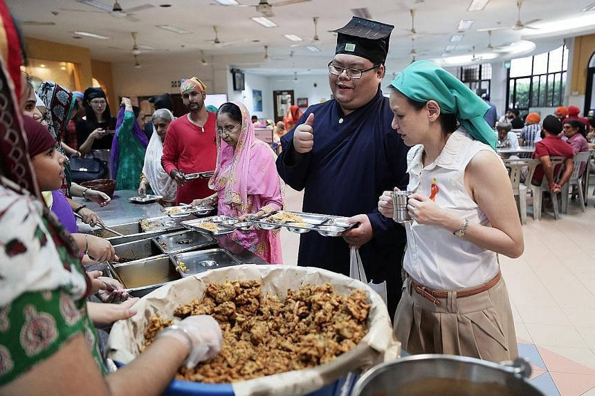 Taoist priest-in-training Kendrick Goh, 23, and fellow learning journey participant Gwee Siew Theng, 49, being served food by volunteers at Silat Road Sikh Temple yesterday. ST PHOTO: KELVIN CHNG