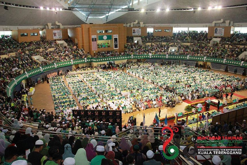 Delegates at the PAS annual assembly in Kuantan on Friday, with party president Abdul Hadi Awang on stage. The delegates were seated at the ground level, with observers and other party members on the higher level.