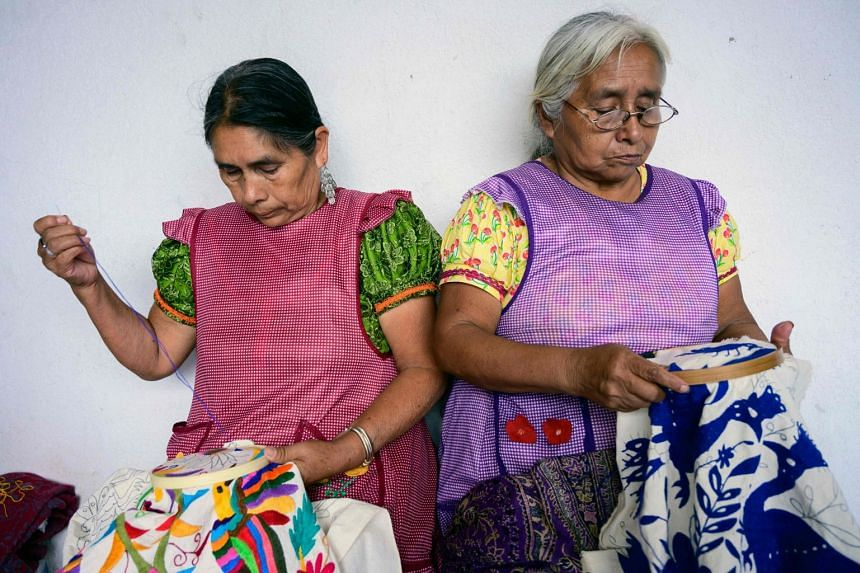 Mexican artisans of the Otomi ethnic group embroider their designs in Tenango de Doria.