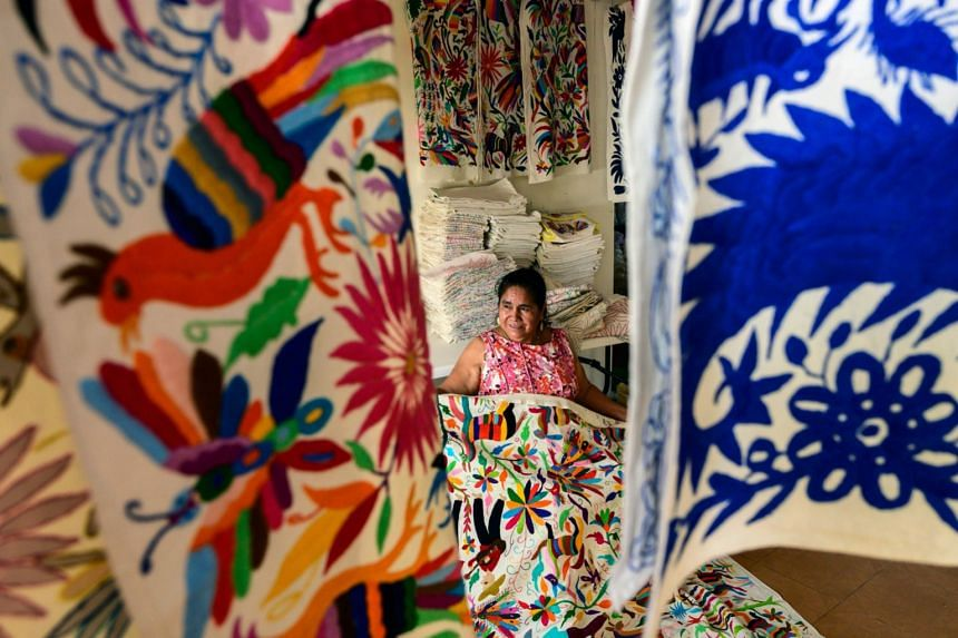 Mexican artisan Glafira Candelaria Jose, of the Otomi ethnic group, shows one of her designs at her workshop in Tenango de Doria,