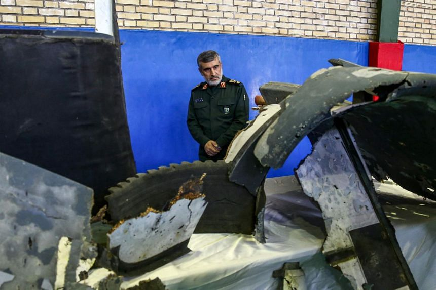 General Amir Ali Hajizadeh, Iran's Head of the Revolutionary Guard's aerospace division, looks at debris from a downed US drone reportedly recovered within Iran's territorial waters and put on display by the Revolutionary Guard in Tehran on June 21,