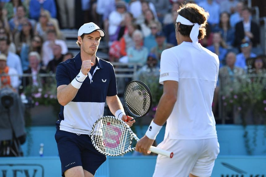 Murray (left) gestures during his match alongside Spain's Feliciano Lopez.