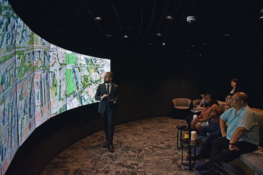 Real estate agency CBRE's new headquarters at Paya Lebar Quarter has various working spaces, such as the cafe and working area, a room which houses a state-of-the-art presentation tool called the Liquid Galaxy (above), and the team totems area where