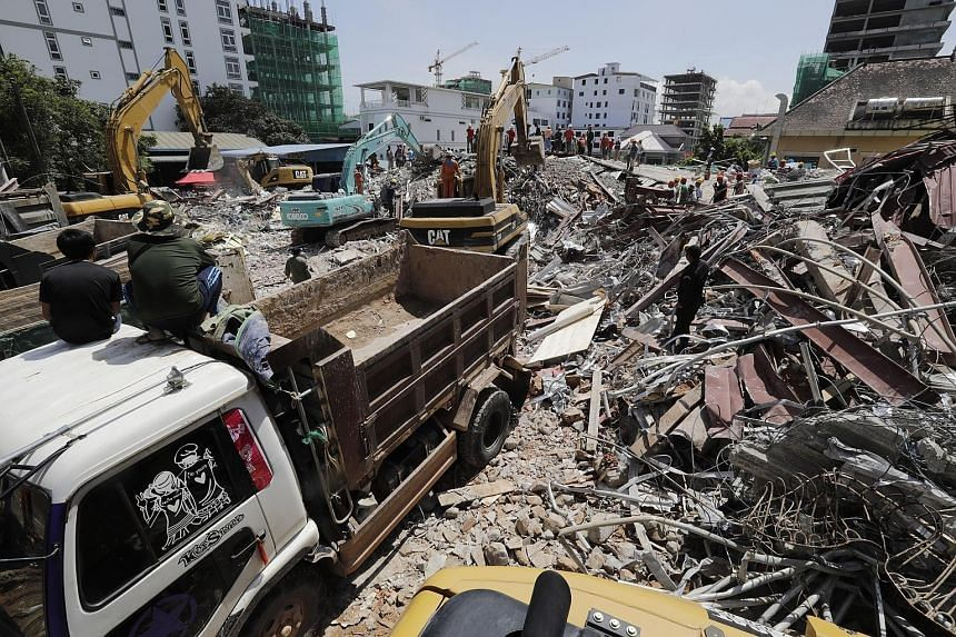 """A Cambodian rescue team (above) searching yesterday for missing workers at the site of the collapsed seven-storey building. (Below) A woman sobbing at a hospital after learning that her niece had died in the tragedy. A provincial official said """"teams"""