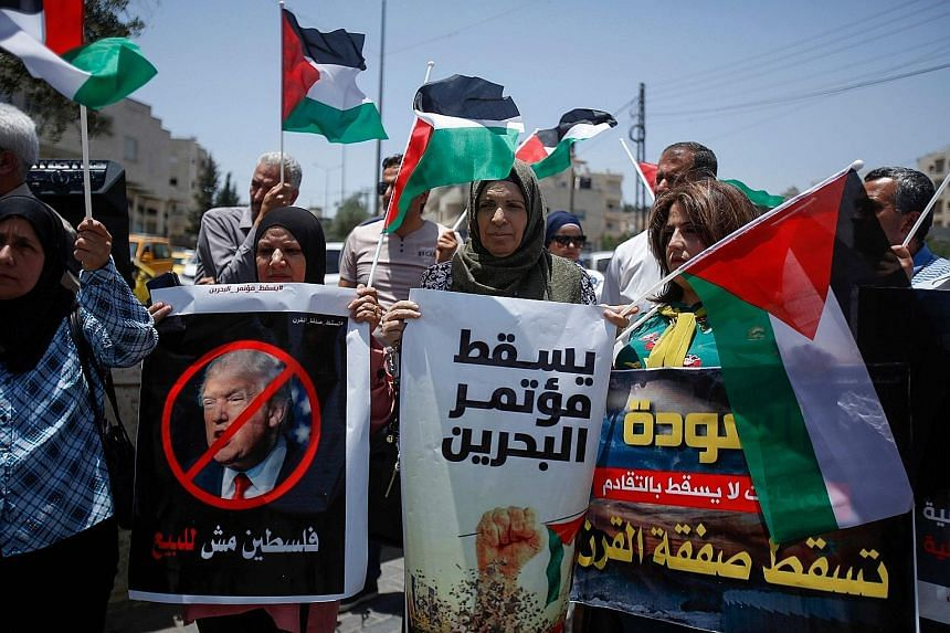 """Demonstrators with banners, including one that reads """"Palestine is not for sale"""" in Arabic, protesting in Bethlehem. Arab analysts believe the economic plan being put forward by the US is an attempt to buy off opposition to Israel's occupation of Pal"""