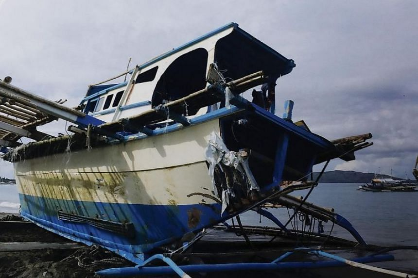 The damaged fishing boat Gem-Vir on the shore of San Jose town in the Philippines.