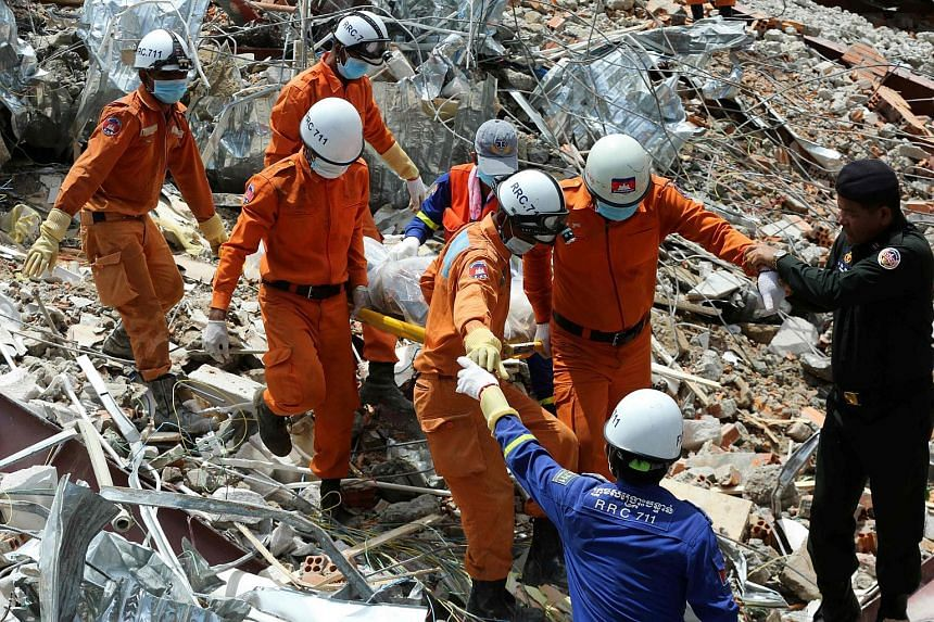 Rescue workers carrying the body of a victim dug out from debris of the seven-storey Chinese-owned construction site.