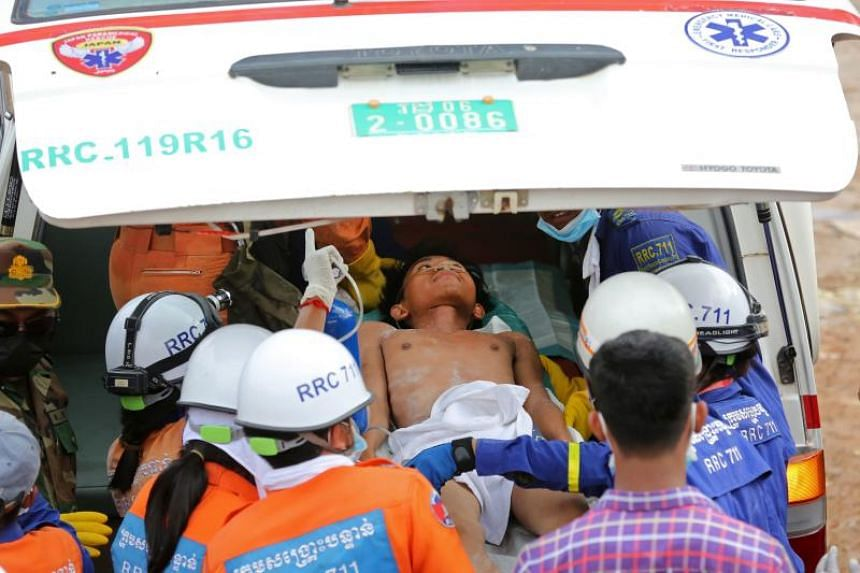 A survivor is placed in an ambulance after being pulled out of the rubble of a collapsed building in Sihanoukville, on June 24, 2019.