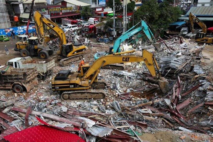 Rescue workers use earthmovers to clear debris as they search for victims a day after an under-construction building collapsed in Sihanoukville, on June 23, 2019.