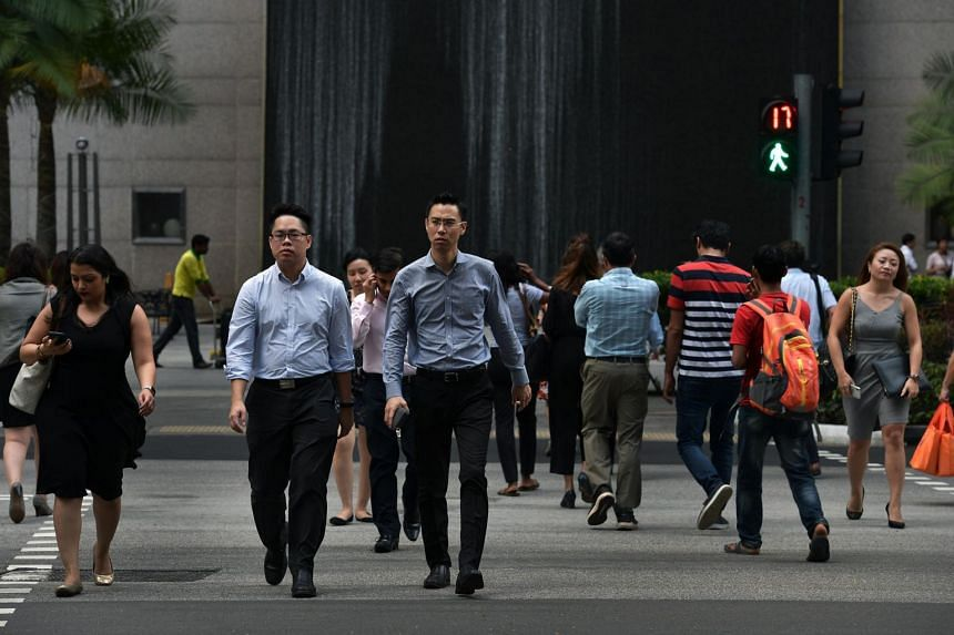 Office workers cross the road in Singapore's financial district on Feb 14, 2018.