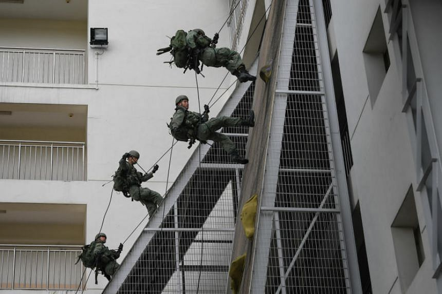 Commandos rappelling during a demonstration at Pasir Ris Camp. The 1st Commando Battalion chalked up its 16th consecutive win for the Best Combat Unit.