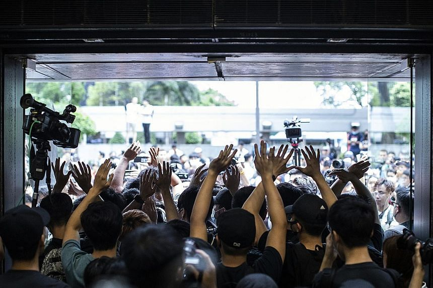 Protesters raising their hands as they blocked an entrance into Hong Kong's Revenue Tower yesterday. PHOTO: BLOOMBERG