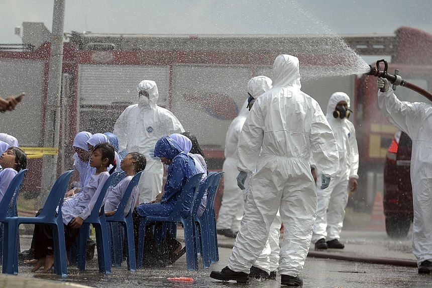 Pupils being decontaminated outside Pasir Gudang Indoor Stadium. Schools in the area have been closed, but officials are no closer to the source of the problem. Medical staff transferring a child from a medical tent to a waiting ambulance at the Pasi