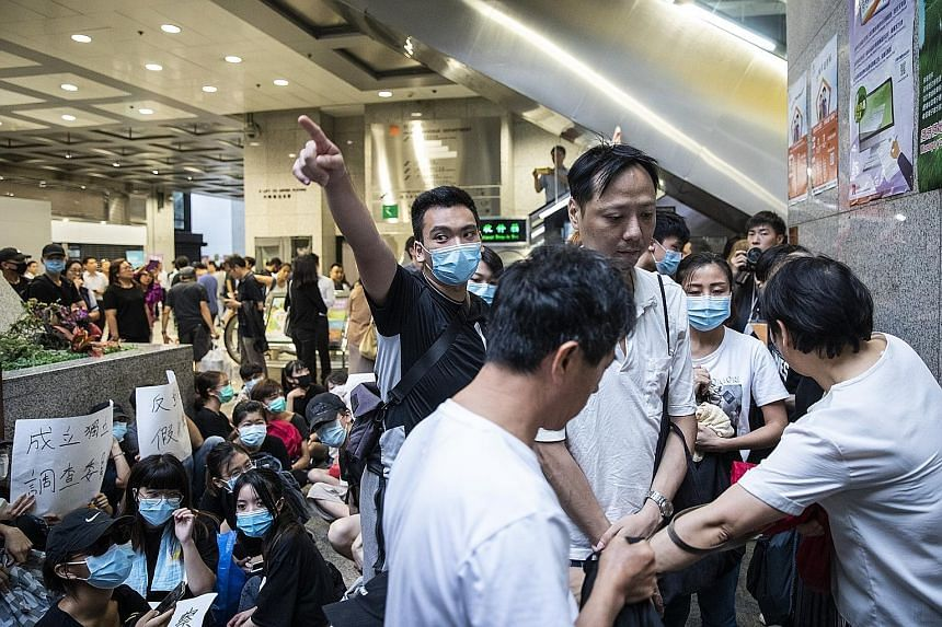 Protesters directing members of the public as they block an entrance inside Hong Kong's Revenue Tower during a demonstration against a controversial extradition Bill yesterday. The protesters are planning another demonstration tomorrow to raise aware
