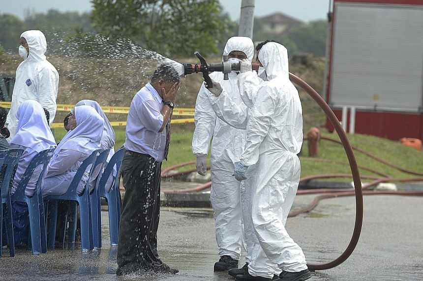 Health officials carrying out decontamination work yesterday at Johor's Pasir Gudang Indoor Stadium, where an early treatment centre was set up for dozens of students suffering from vomiting and breathing difficulties after attending schools nearby.