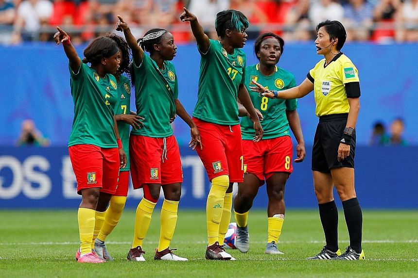 Cameroon's Gaelle Enganamouit (No. 17), Raissa Feudjio (No. 8) and teammates remonstrating with Chinese referee Liang Qin after England's second goal was awarded following a VAR review. They then appeared to threaten to walk off although this was ref
