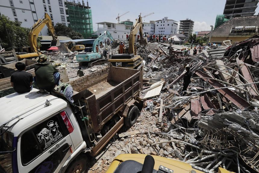 A Cambodian rescue team searches for missing workers at the site of a collapsed building in Preah Sihanouk province, on June 23, 2019.