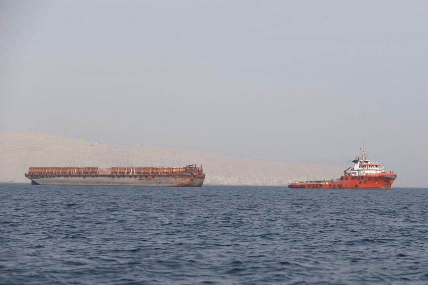 A tugboat moves cargo towards the Strait of Hormuz off the coast of Musandam province, Oman, on July 20, 2018.