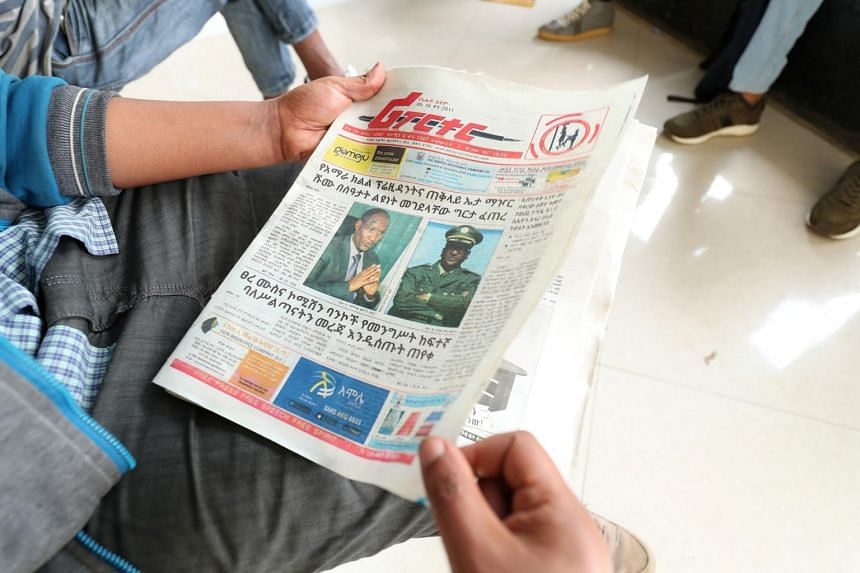 A man reads a newspaper with the pictures of Amhara state President Ambachew Mekonnen (left), killed in the region's main city Bahir Dar, and of Army Chief of Staff Seare Mekonnen, who was shot by his bodyguard, on a street in Addis Ababa, Ethiopia,