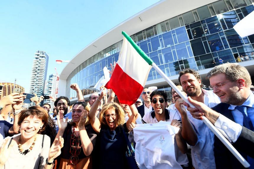 Italians celebrate in Milan after the city was announced as the winning candidate to host the 2026 Winter Olympic Games.