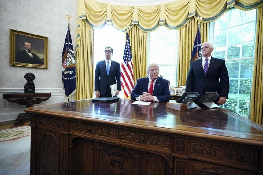 """US President Donald Trump, with US Vice-President Mike Pence (right) and US Secretary of Treasury Steven Mnuchin, at the White House on June 24, 2019, before signing """"hard-hitting sanctions"""" on Iran's Supreme Leader."""