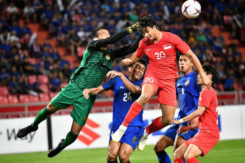 The national football teams of Singapore (in red) and Thailand in action during the Asean Football Federation Suzuki Cup in 2018.