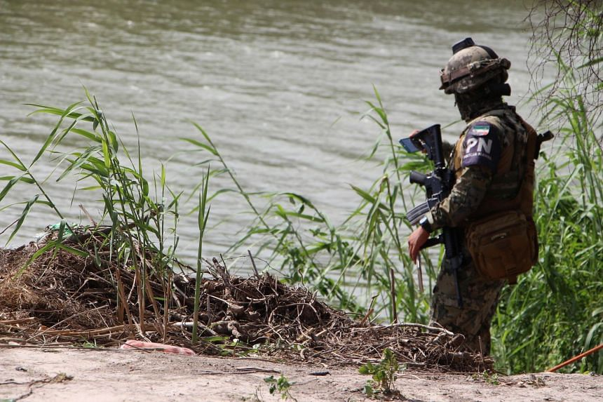 A Mexican policeman patrols the area where the bodies of a presumed migrant and his baby were found on a bank of the Rio Grande in Matamoros, Mexico, on June 24, 2019.