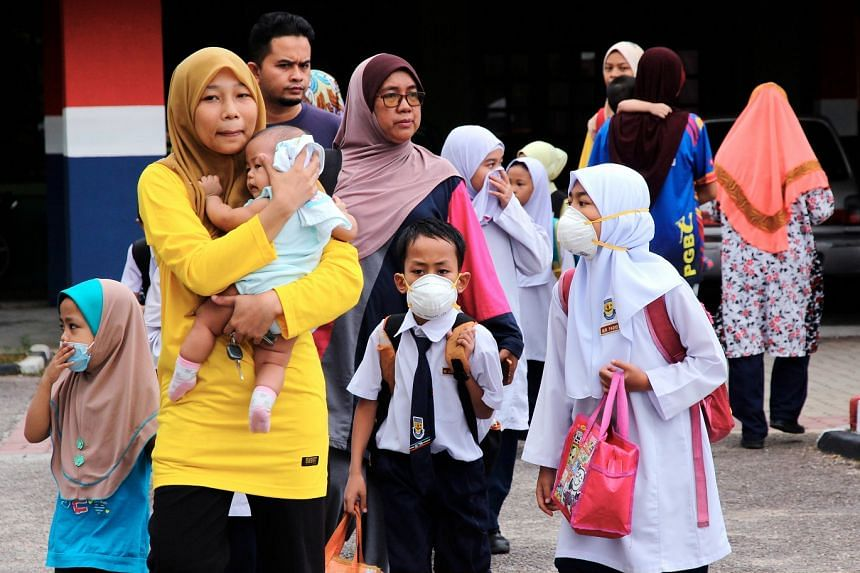 Parents taking their children home after receiving reports of pupils experiencing breathlessness and nausea in school. As of 3pm yesterday, 75 students were referred to Hospital Sultan Ismail, with only four still warded.