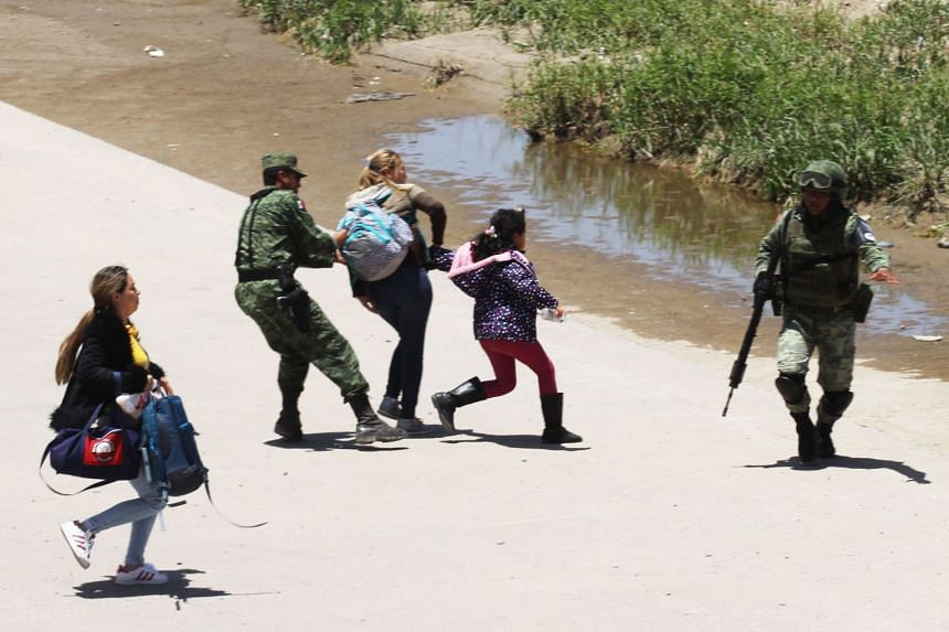 Mexican national guardsmen prevent Central American migrants from crossing the Rio Bravo river, June 21, 2019.