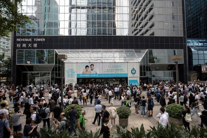 Staff and visitors of the Revenue Tower, a government building, wait outside as protesters occupy the lobby of the building during a protest against an extradition Bill in Hong Kong on June 24, 2019.