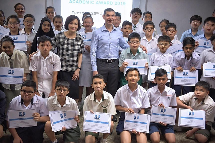 Ms Sarah Chua, vice-president of IT and Mobile, Samsung Electronics Singapore, and Mr Warren Fernandez, chairman of The Straits Times School Pocket Money Fund and editor of The Straits Times, with some of the cash award recipients yesterday. In total
