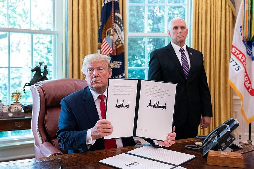 US President Donald Trump with the executive order he signed on Monday to impose further sanctions on Iran. With him in the Oval Office at the White House is Vice-President Mike Pence. US National Security Adviser John Bolton yesterday repeated earli