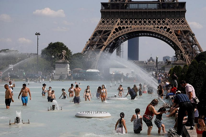 People cooling off in the Trocadero fountains across from the Eiffel Tower in the French capital Paris yesterday. Temperatures are soaring in Europe, and officials on Monday urged vigilance ahead of even hotter conditions forecast later in the week.