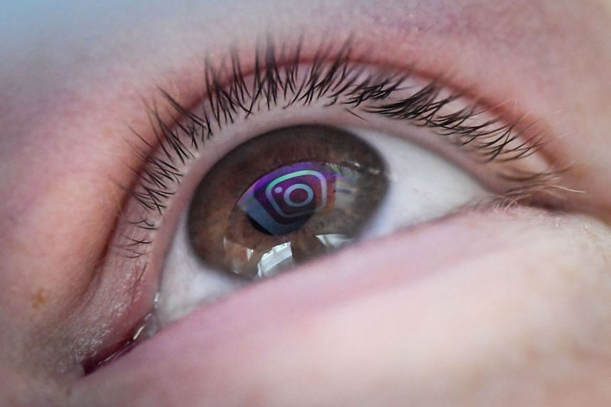 The logo of US social network Instagram is reflected in a woman's eye.