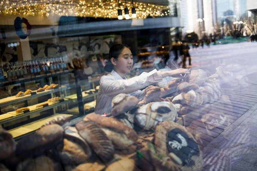 A waitress working in a bakery owned by Chinese billionaire Hu Keqin in Beijing, on Jan 30, 2018.