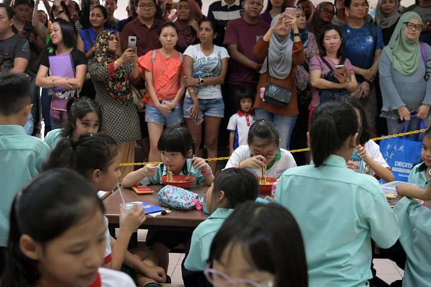 Primary one students dining and interacting at a school canteen while their parents look on.