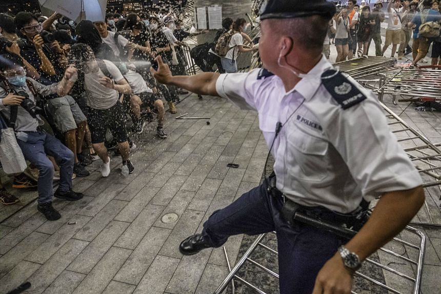 A police officer using pepper spray during clashes with protesters in Hong Kong this month. Britain wants an independent investigation into police violence and will not issue export licences for crowd-control equipment to Hong Kong unless it is satis