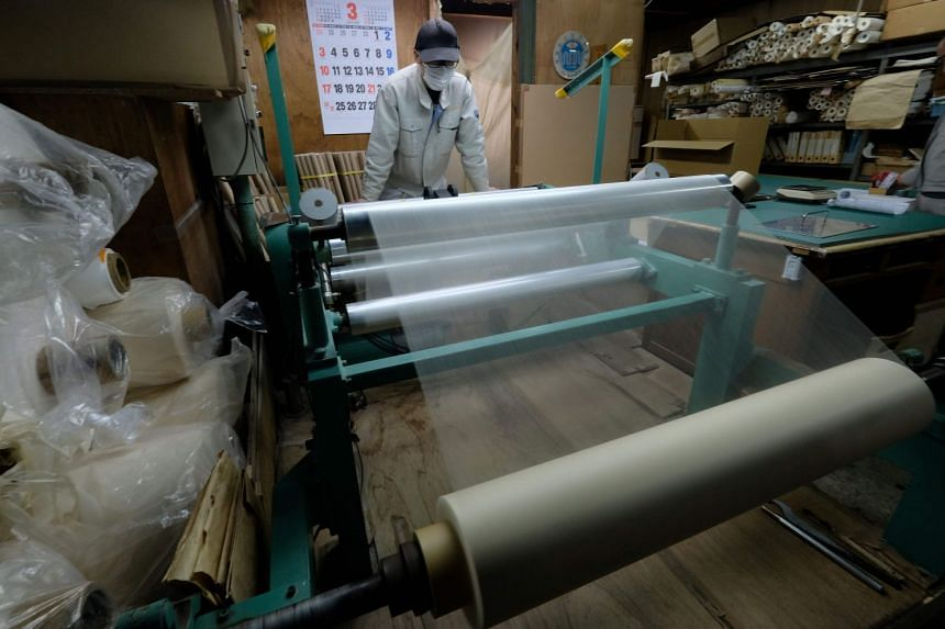 A worker checking a roll of the world's thinnest washi paper at the Hidaka Washi factory in Hidaka, Kochi prefecture.