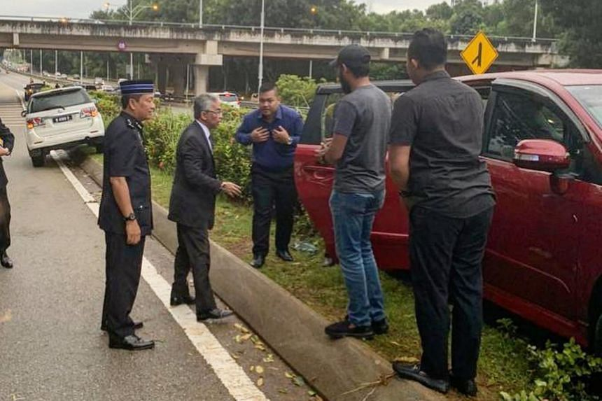 Sultan Abdullah Ri'ayatuddin (second from left), who was on his way to a weekly pre-Cabinet meeting with Prime Minister Mahathir Mohamad, stopped his car to offer help to the accident victim.