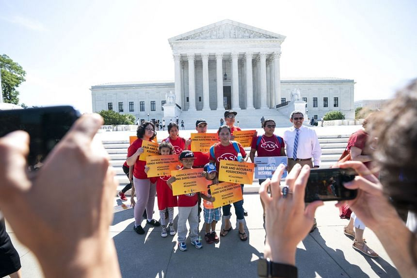 Immigration activists gather outside the US Supreme Court to await the justices' ruling.