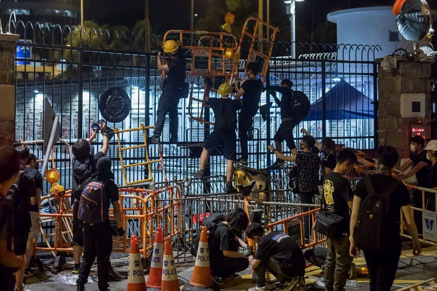 Demonstrators set up barriers at the entrance of the police headquarters during a protest in Hong Kong.