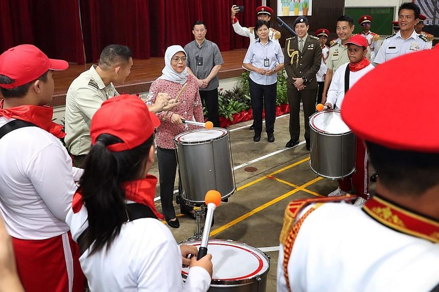 President Halimah Yacob trying out drumming with performers from a combined drum band for this year's National Day Parade, at APSN Tanglin School yesterday. The band consists of 24 participants from APSN Tanglin - a special education school for those