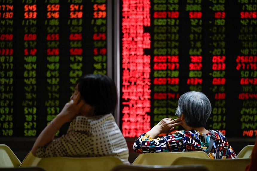 Investors resting on a chair in front of screens showing stock market movements at a securities company in Beijing, China.