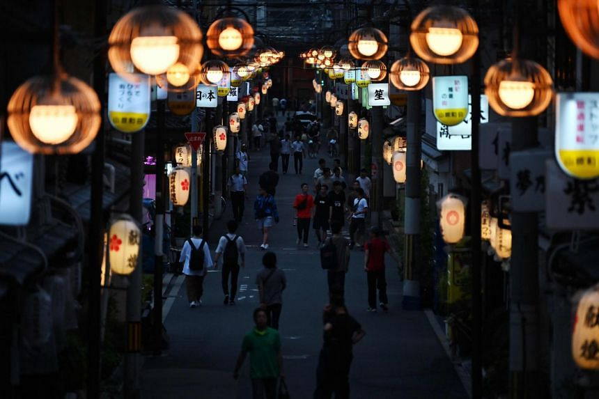 People walking through a red light district in Osaka, on June 26, 2019.
