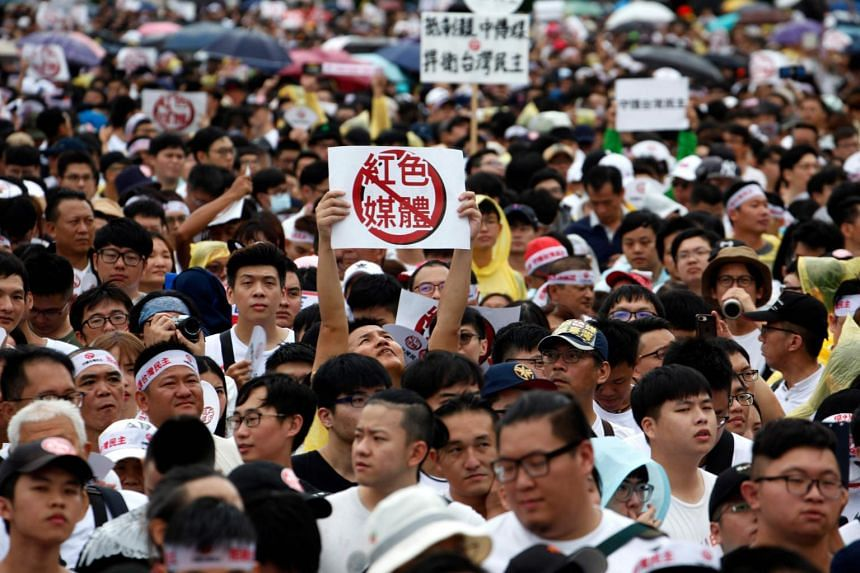 """Protesters hold placards with messages that read """"reject red media"""" during a rally in front of the Presidential Office building in Taipei, on June 23, 2019."""