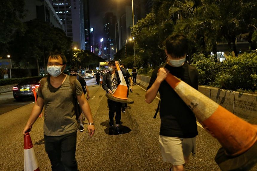 Protesters carrying traffic cones gather outside the Wan Chai Police Headquarters after a rally in Hong Kong, on June 26, 2019.