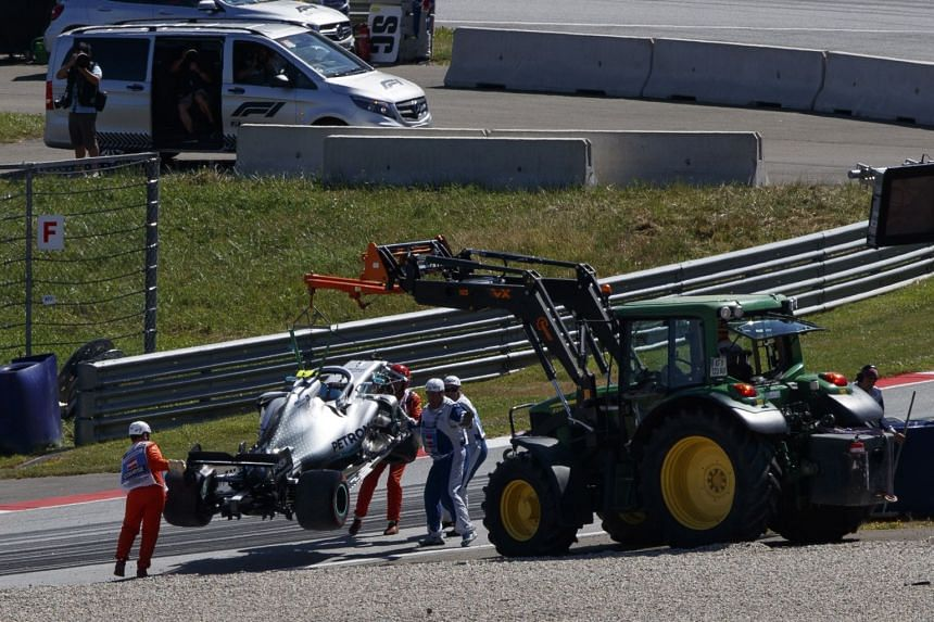 Marshals lift up Bottas' car during the second practice session.