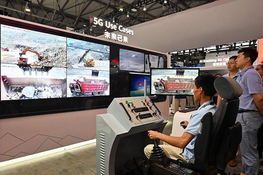 A user trying out a remote control machine with 5G technology at a Huawei booth at the Mobile World Congress in Shanghai on Wednesday. Papers from published periodicals and online research databases have shed light on how staff at Huawei teamed up wi