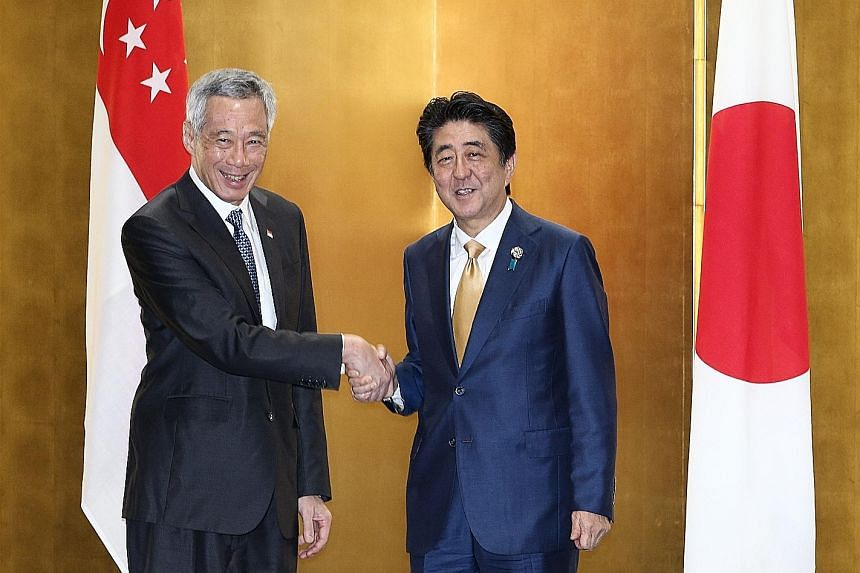 Prime Minister Lee Hsien Loong being welcomed by Japanese Prime Minister Shinzo Abe yesterday upon his arrival in Osaka. PM Lee is attending the Group of 20 Summit at the invitation of Mr Abe.